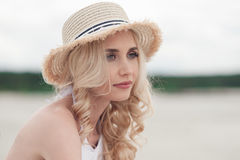 Portrait of a girl blondes on the beach. Portrait of beautiful girl blonde in straw hat sitting on beach Royalty Free Stock Image