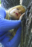 Portrait the girl with blue eyes. The girl in a wood near to a tree. Eyes of the pigeons of the sky. A light hair. The beautiful face of the young girl. Ideally stock images