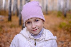 Portrait of a girl with blue eyes who stands in the autumn forest. Teenager girl in a hat and jacket against a background of royalty free stock image