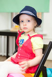 Portrait of girl in blue hat sitting on chair stock image