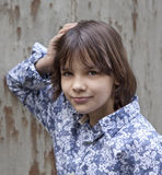 Portrait of the girl in the blue shirt. On the background of the wall Stock Photo