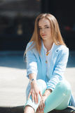 Portrait of a girl in a blue suit,sitting near the office Stock Image
