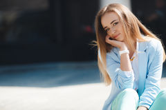 Portrait of a girl in a blue suit,sitting near the office Royalty Free Stock Photography