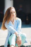 Portrait of a girl in a blue suit,sitting near the office Stock Photos