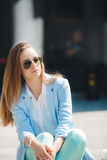 Portrait of a girl in a blue suit,sitting near the office Royalty Free Stock Photo