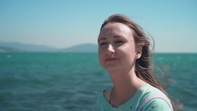 Portrait of a girl in a blue T-shirt on the seashore. Girl on the background of the sea, mountains and sky. stock video footage