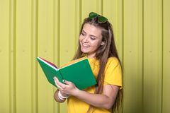 Beautiful young woman reading a book on pastel yellow background. stock image