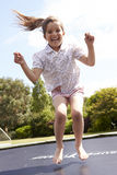 Portrait Of Girl Bouncing On Trampoline In Garden Royalty Free Stock Image