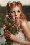 Portrait of a girl with a bouquet of clover at sunset. Royalty Free Stock Images