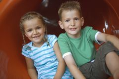 Portrait of a girl with a boy sitting in a tubular slide Royalty Free Stock Photos