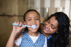 Portrait of girl brushing teeth with mother in bathroom Stock Photo