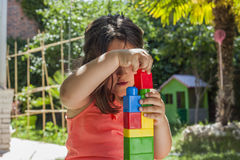 Portrait girl building with plastic construction toys in garden Royalty Free Stock Photo