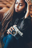 Portrait of a girl with camera and in fashionable style. Portrait of a girl with camera sitting down the floor Royalty Free Stock Photography