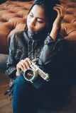 Portrait of a girl with camera and in fashionable style. Portrait of a girl with camera sitting down the floor Royalty Free Stock Photos