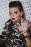 Portrait of a girl in camouflage clothing through the mesh Stock Image