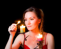 Portrait of a girl candle lights a match Stock Photography