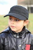 Portrait of girl in cap. Cute little kid - girl clothed in black winter jacket and black baseball cap Stock Photography