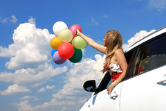 Portrait a girl in the car with colorful balloons Stock Images