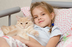 Portrait of the girl with a cat lying in bed Stock Image