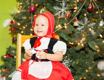 Portrait of girl child in suit a red hat for Christmas around a fir-tree decorated. Kid on holiday new year Stock Photo