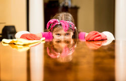 Portrait of girl cleaning house checking table surface Royalty Free Stock Photo