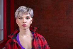 Portrait of a girl close-up of a beautiful young blonde with short hair in a red plaid shirt, hipster royalty free stock image