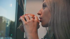 Portrait of a girl close-up with a hamburger in his hand. A young pretty woman eating a hamburger at a cafe. Food, Fast stock video footage
