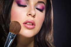 Portrait of girl with closed eyes applying bright make-up Stock Photography
