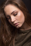 Portrait of the girl with closed eyes on a black background, gre Stock Images