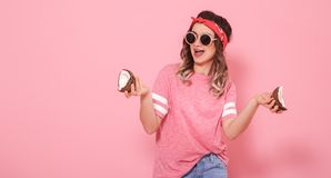 Portrait of a girl with coconuts, on a pink background stock image