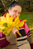 Portrait of a girl. In a colorful knitted scarf with a bouquet of yellow leaves Royalty Free Stock Photography