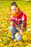 Portrait of a girl. In a colorful knitted scarf with a bouquet of yellow leaves royalty free stock photos