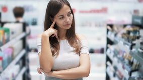 Portrait of girl in cosmetics shop thinks which product to buy, slow motion. Woman shopper doubts and compares stock footage
