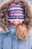 Portrait of girl with covered face with her hat outdoors. In the wintertime Stock Photo