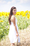 Portrait of a girl in cropland. Near sunflower field with a hat royalty free stock image
