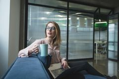 Girl with a cup of coffee in her hands and a laptop on the background of the office. Freelancer works stock photos