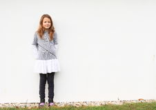 Portrait of a girl. Cute little kid - smiling brunette girl in grey t-shirt, white skirt and black pants with white wall behind Royalty Free Stock Photos