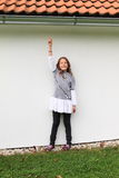 Portrait of a girl. Cute little kid - smiling brunette girl in grey t-shirt, white skirt and black pants with white wall behind showing up to roof with eaves Stock Photography