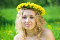 Portrait girl in dandelion chaplet. Portrait of blonde girl in dandelion chaplet against nature Royalty Free Stock Photography