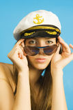 Portrait of the girl in dark glasses and a sea peak-cap. The attractive young girl Royalty Free Stock Image
