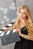 Portrait of a girl director with an empty clapperboard. Lovely girl blonde assistant director holding an empty clapperboard. Close-up portrait. The concept of Royalty Free Stock Image