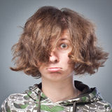 Portrait of a girl with disheveled hair, emotions cool in Studio on gray background Stock Photo