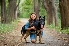 Girl with a dog by a German shepherd in the summer. Royalty Free Stock Images