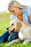 Portrait of girl with dog on grass Stock Photography