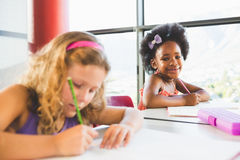 Portrait of girl doing homework in classroom Royalty Free Stock Photo