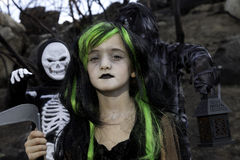 Portrait of girl dressed up as witch while her friends dressed up in skeleton costume Stock Image