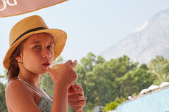 Portrait of girl are drinkig fresh juice, summer mountain landsc Royalty Free Stock Photo