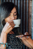 Portrait of a girl drinking coffee in a vintage cafe on the terrace in Asia. Sniffs, drinks. royalty free stock photo