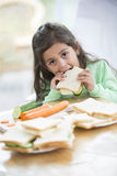 Portrait of girl eating sandwich at home Royalty Free Stock Images