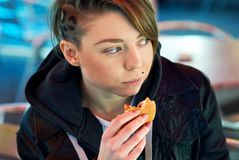 Portrait of girl with eats burger on the terrace Royalty Free Stock Photography